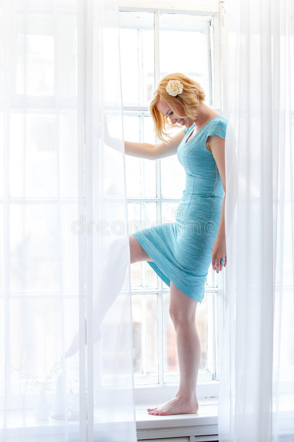 Romantic portrait of tender lady standing behind white curtains royalty free stock image
