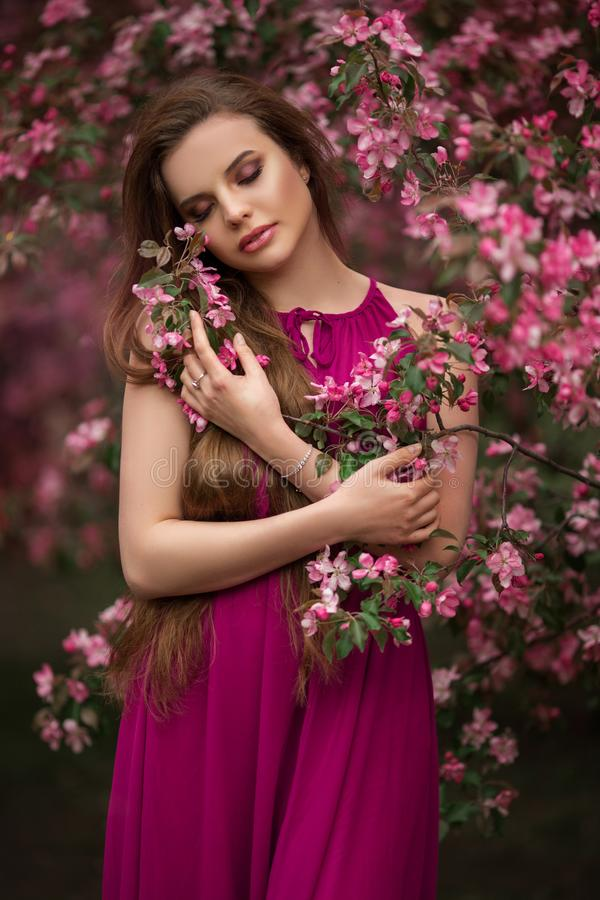 Romantic portrait of young attractive woman in blooming pink apple garden royalty free stock photography