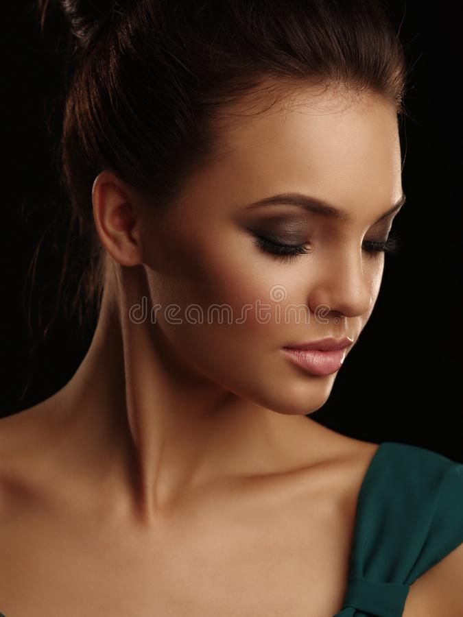 Romantic portrait of a young beautiful girl with mild features collected hair and expressive make up on the black background royalty free stock images