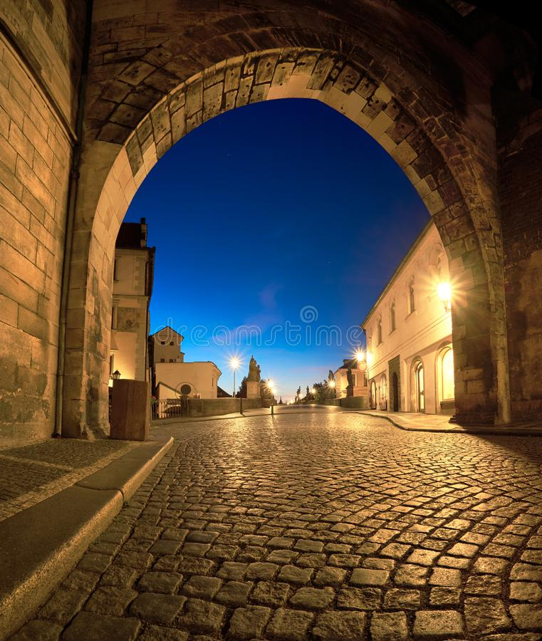 Romantic Prague at dawn, entrance to Charles Bridge through the illuminated arch of Lesser Town Bridge Tower. Early in the morning. Panoramic image, square stock photography
