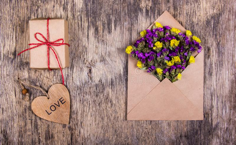 A romantic premise, an envelope with flowers, a gift and a wooden heart. St. Valentine`s Day. Templates and backgrounds royalty free stock photos