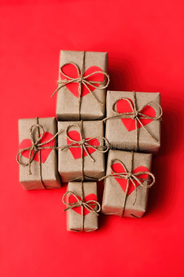Romantic presents set. Gift boxes wrapped in brown craft paper and tie hemp string. Carton hearts. Red solid background. Delivered parcels stock image