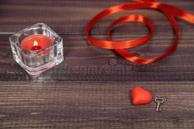 Red valentine, candle, ribbon and a silver key. Romantic preset with small red valentine, candle, ribbon and a silver key royalty free stock photos