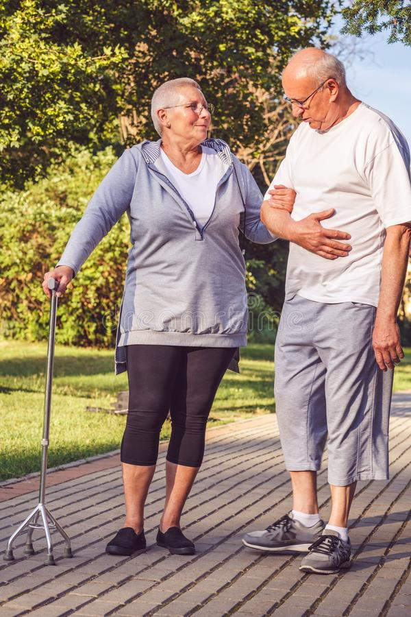 Romantic relationships- elderly couple walking through the park stock photos