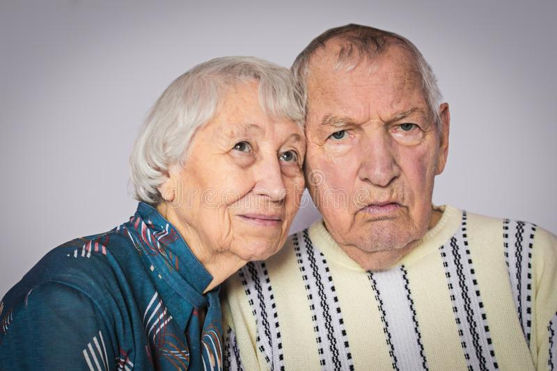 Romantic sad elderly couple sitting close together royalty free stock photos