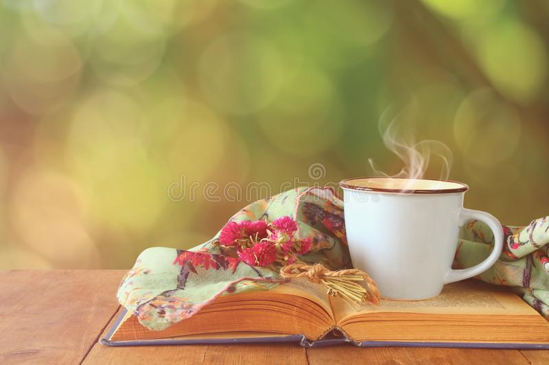 romantic scene of cup of coffee next to old book in front of countryside bokeh landscape background. royalty free stock image