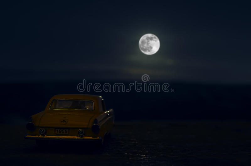 Romantic scene of old vintage car with couple inside and Moon on sky at night. Silhouette love and car on Full Moon Background. Se. Lective focus stock photo