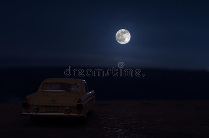 Romantic scene of old vintage car with couple inside and Moon on sky at night. Silhouette love and car on Full Moon Background. Se. Lective focus stock photography