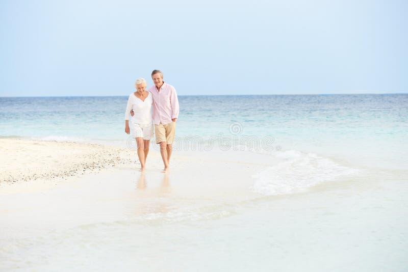 Romantic Senior Couple Walking On Beautiful Tropical Beach