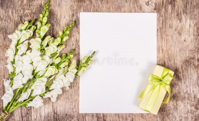 Romantic set. Copy space. Gift box with green bow. Love letter and flowers. Clean paper background stock photo