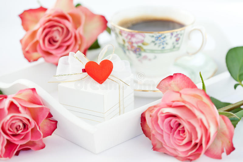 Romantic setup. Coffee in bed with gift and roses royalty free stock image