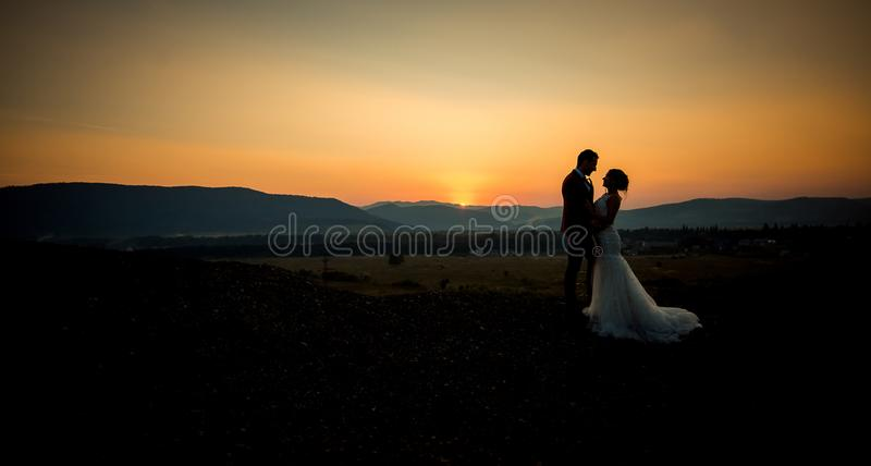 Romantic shot of the beautiful newlyweds hugging at the edge of the mountains during the sunset. royalty free stock image