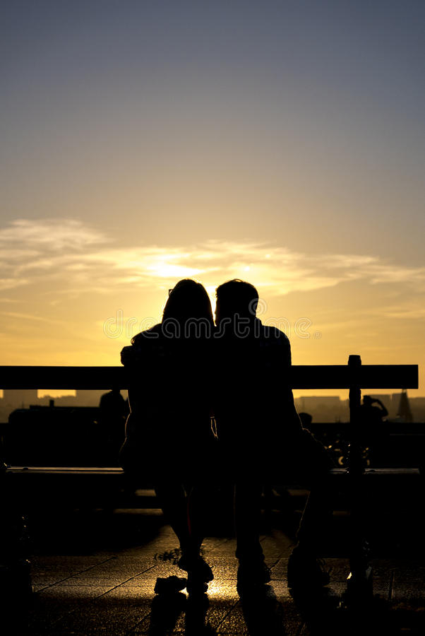 Romantic silhouette of couple sitting with sunset and city in th. Silhouette of young couple sitting on a bench in Brussels with sunset and urban city in the stock photo