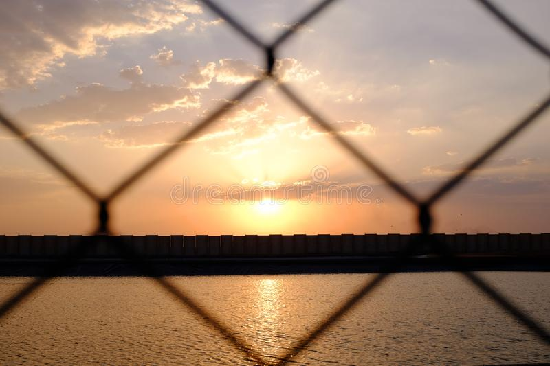 Romantic sky at sunset with pink, orange, yellow and purple hues behind wire fence. Romantic and colorful sky at sunset with pink, orange, yellow and purple hues stock images