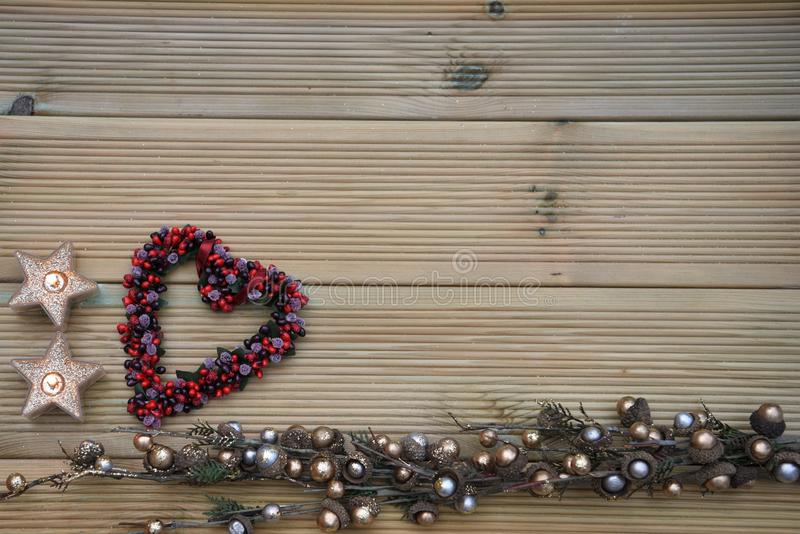 Christmas photography with silver and gold colored acorn tree ornament on natural rustic wood background with red berry love heart royalty free stock image