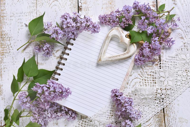 Romantic style flat lay with lilacs and a notebook for own text. Romantic style flat lay with purple lilac, a heart and a notebook with space for own text on stock images