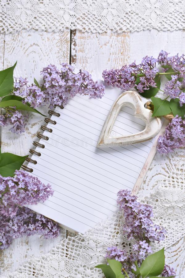 Romantic style flat lay with lilacs and a notebook for own text. Romantic style flat lay with purple lilac, a heart and a notebook with space for own text on stock image