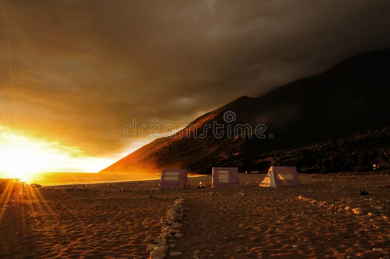 Romantic sunset in empty beach in Albania. Natural light rays shining to three tents and mountains hidden in clouds to background. Dark is coming. Photo taken stock image