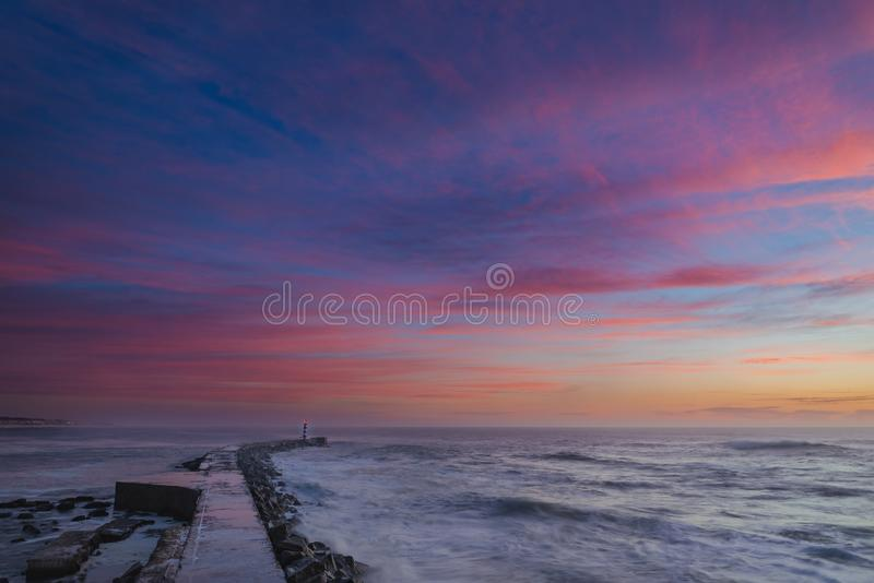 Romantic sunset over the Lighthouse bay. Seascape photography colorful sunset with clouds reflecting the colors of the sunlight stock photography