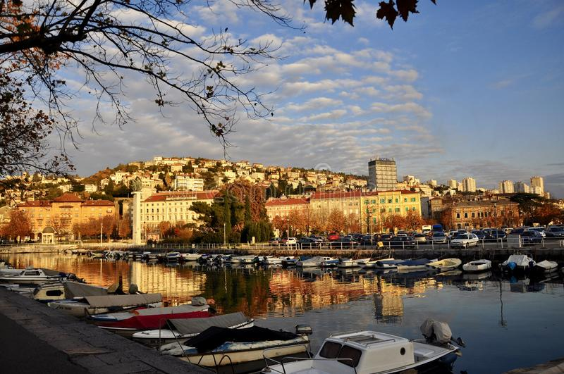 The Water Mirror at sunset in Rijeka. Sunset over the waterfront with reflection of buildings in calm water and ships. The Water Mirror at sunset in the city royalty free stock image