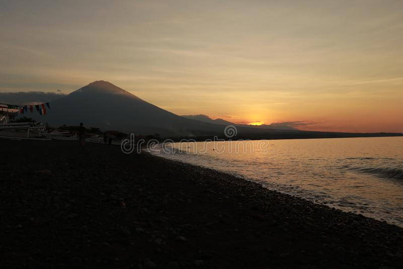 Romantic sunset on the sea coast in Indonesia. Surfer goes to enjoy paddleboard at sunset.Coastline panorama with majestic volcano royalty free stock images