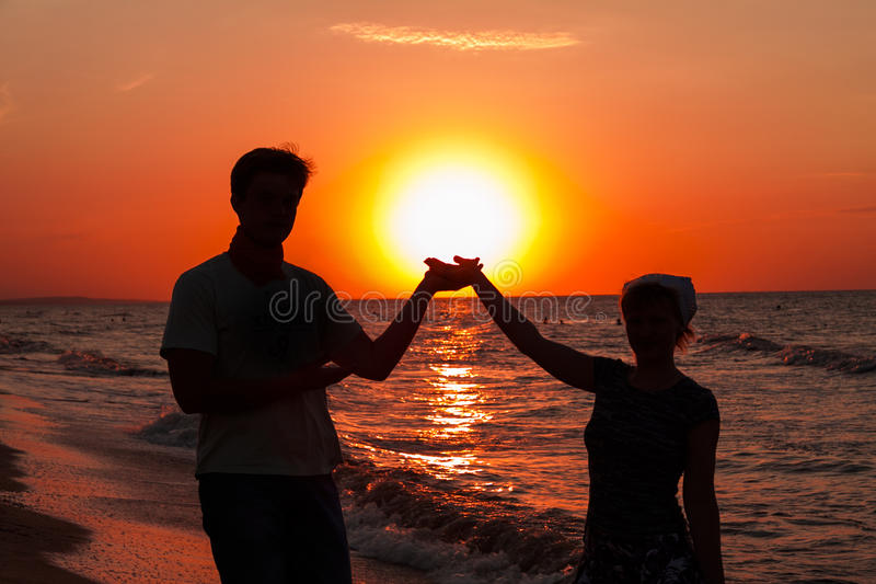 Romantic sunset. Silhouettes of the romantic pair holding the sun in hands at coast of sea of Azov