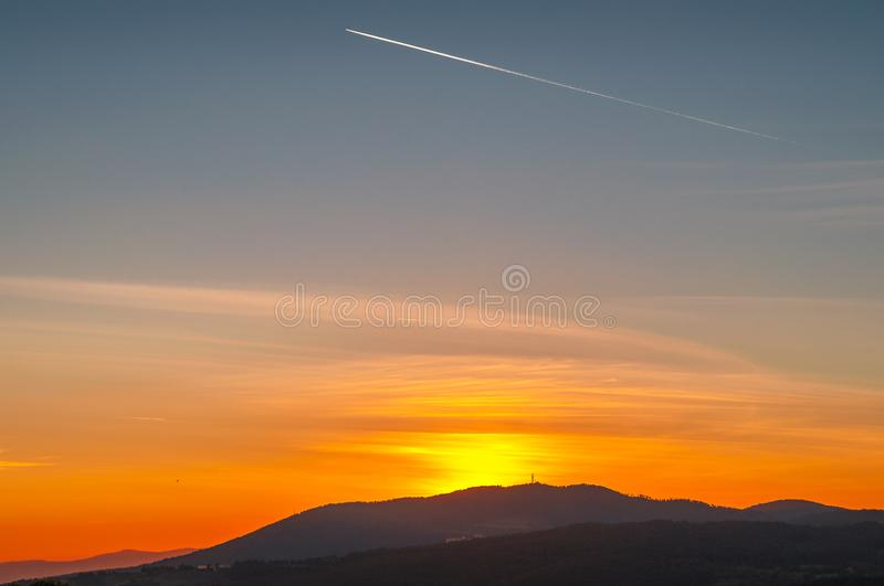 Romantic sunset sky with airplane trail and mountains on the background stock photography
