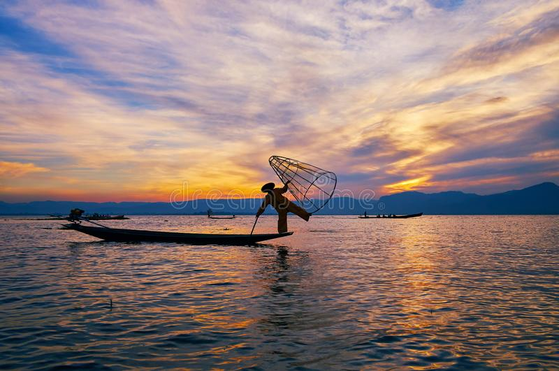 Enjoy the fishing on Inle Lake, Myanmar. Romantic sunset trip on Inle Lake is best opportunity to watch the art of local fishing - one leg paddling and tricks stock photos