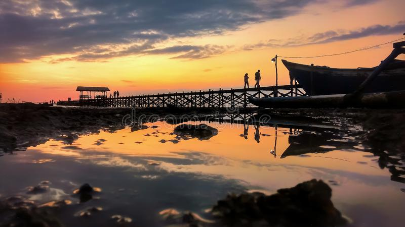 Romantic sunset at untia beach, a recommended tourist attraction when you visit Makassar, South Sulawesi province, Indonesia. royalty free stock image