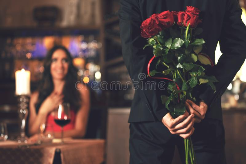 Romantic surprise in the restaurant. Romantic surprise concept - a men holding a bouquet of roses and wants to give it to a women during dinner at a restaurant stock photo