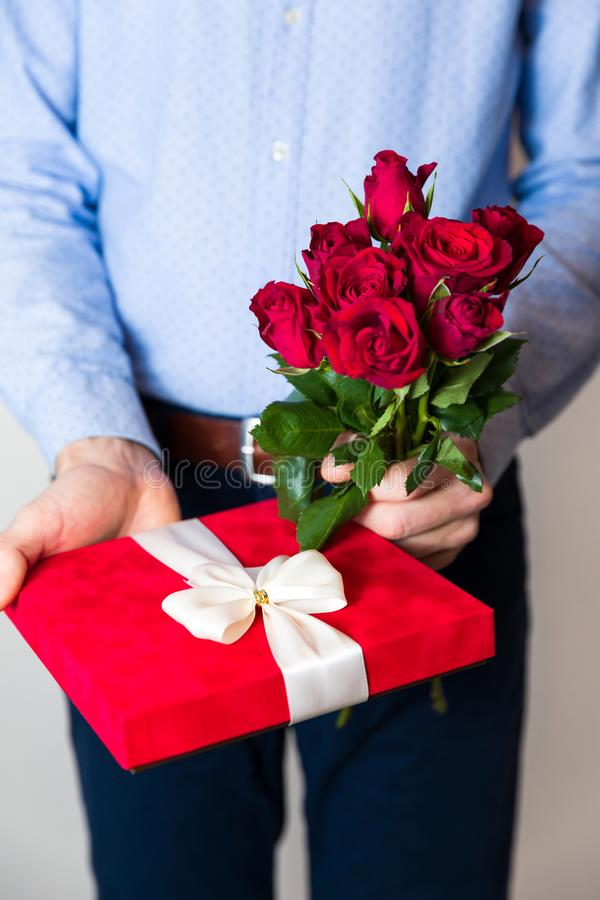 Valentines day surprise, love, handsome man holding romantic gift and red roses bouquet royalty free stock photography