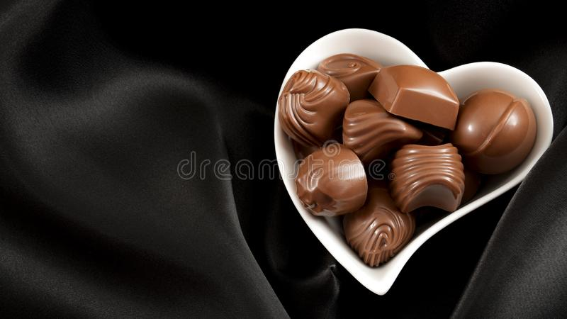 Romantic sweet gifts for Valentines Day concept with a heart shaped bowl filled with chocolate pralines on black silk or satin royalty free stock photography