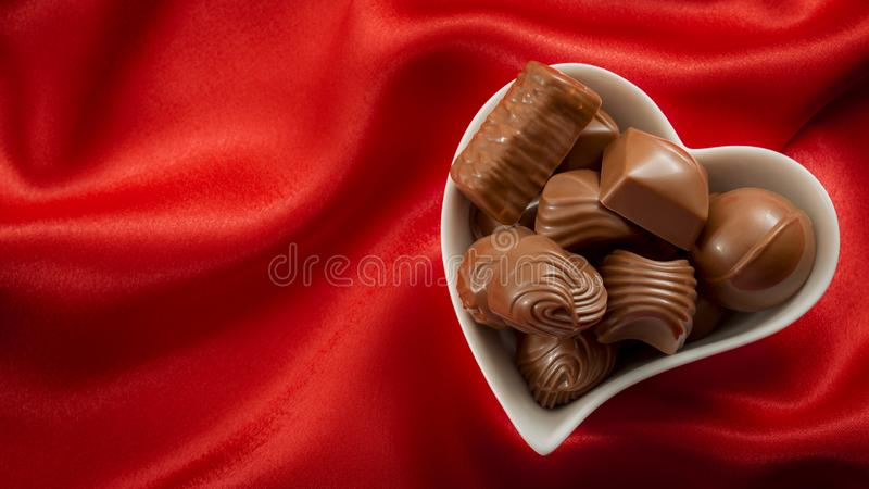 Romantic sweet gifts for Valentines Day concept with a heart shaped bowl filled with chocolate pralines on red silk or satin with royalty free stock photo