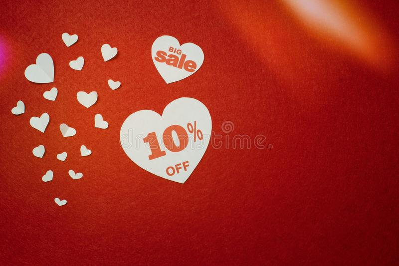 Romantic symbol for sale in the form of a heart with ten percent next to other smaller white hearts on the red background. stock photo