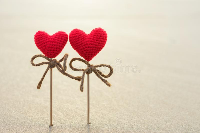 Romantic symbol of two red hearts on the sand surface, stock images