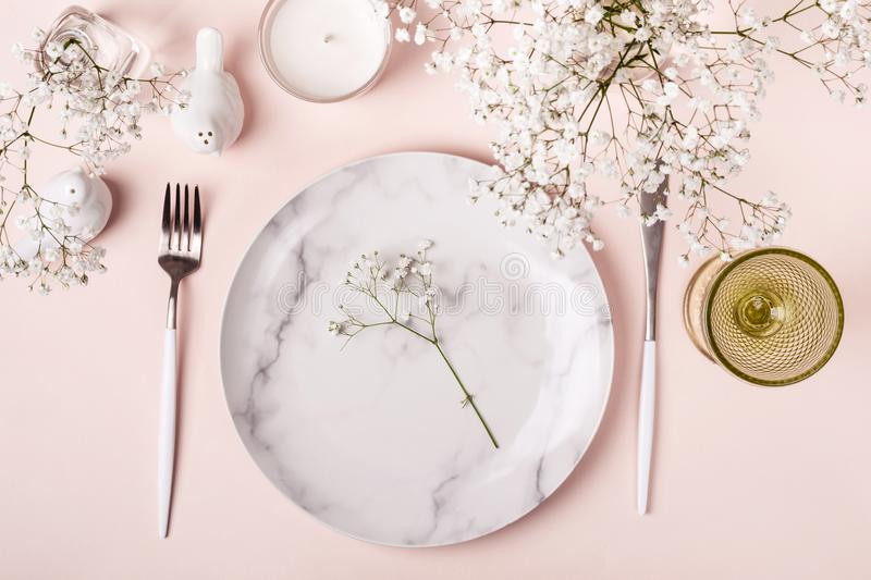 Romantic table setting in pink colors. White flowers decor royalty free stock image