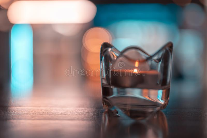 A romantic tealight in the dark on a table. A romantic tealight in the dark on a table royalty free stock images