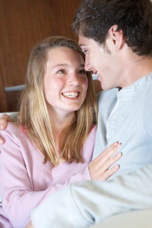 Download Romantic Teenage Couple Sitting On Sofa At Home Stock Photo - Image: 18031616