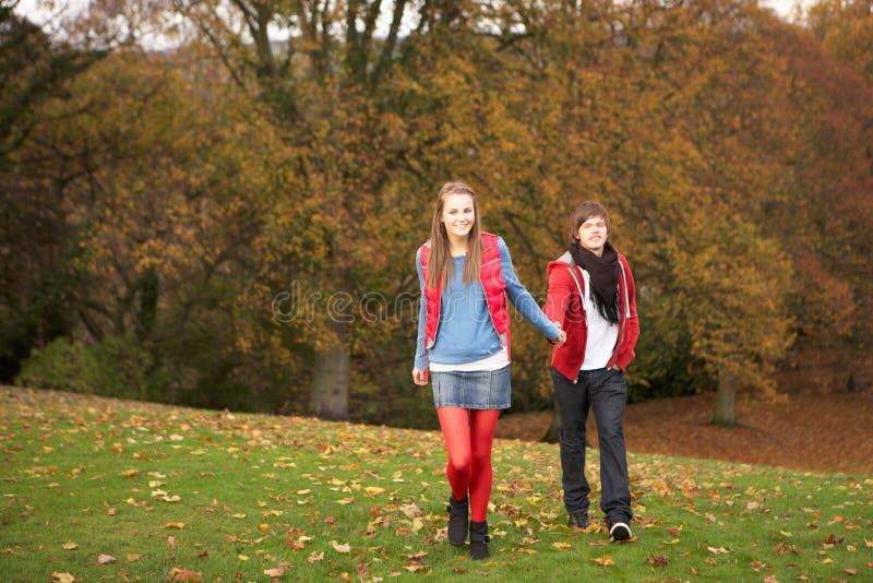 Romantic Teenage Couple Walking Through Autumn