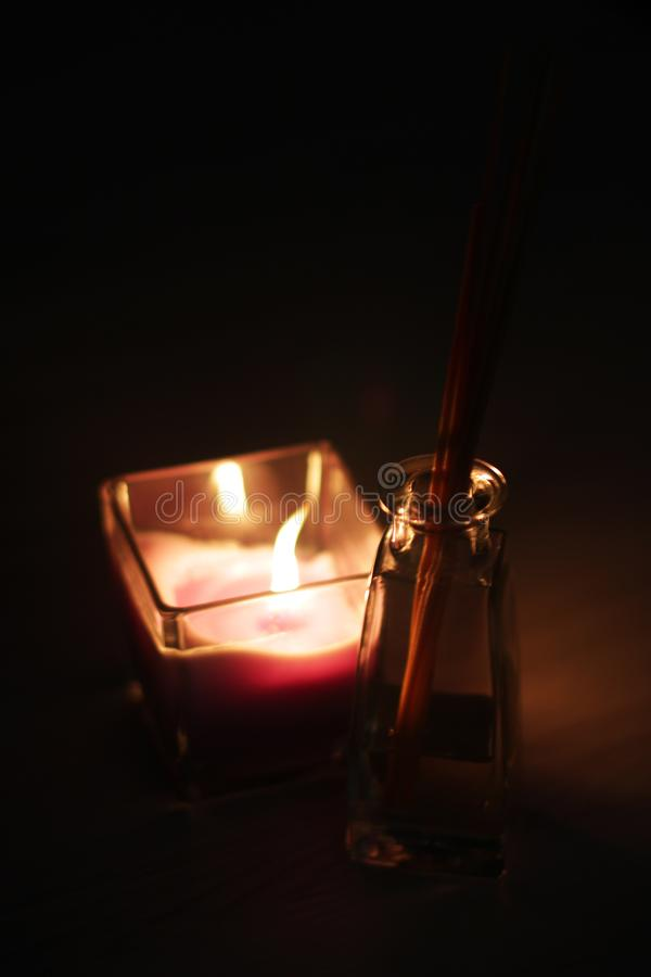Romantic theme: candle and few aroma sticks. Romantic theme: fire of candle and aroma sticks royalty free stock image