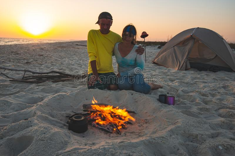 Romantic travelers are sitting next to a burning fire on the beach. And hugging and dreaming during sunset. Amazing adventure in the wild royalty free stock image