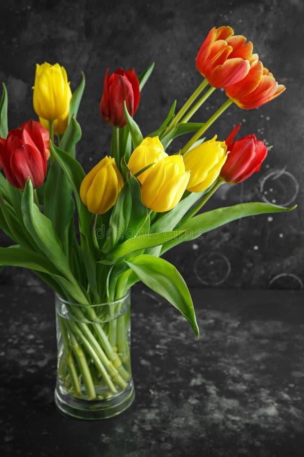 Romantic tulips bouqet on rustic dark background stock image