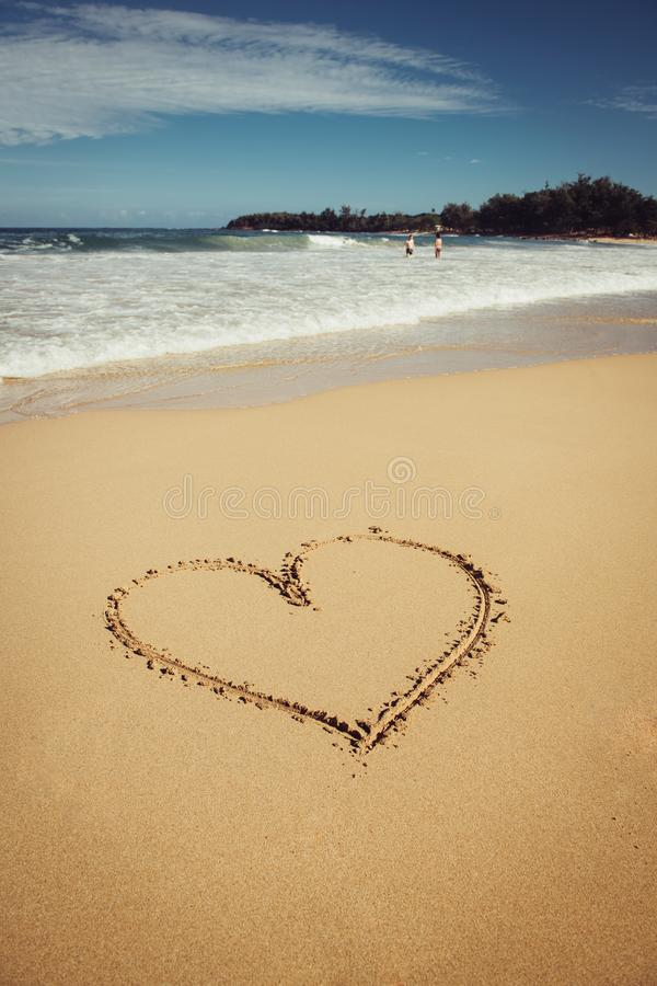 Romantic vacation on Hawaii concept. Heart drawn on ocean beach sand. royalty free stock photography