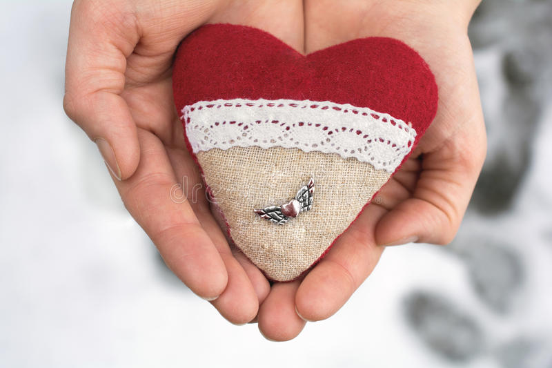 Romantic Valentine Plush Heart With A Winged Metal Heart Holded By Hands In Winter With Snow. Romantic Valentine Plush Heart With Winged Metal Heart Holded By royalty free stock images