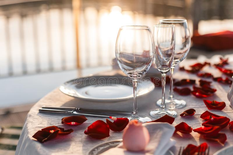 Romantic Valentine`s Day dinner setup with rose petals stock photo