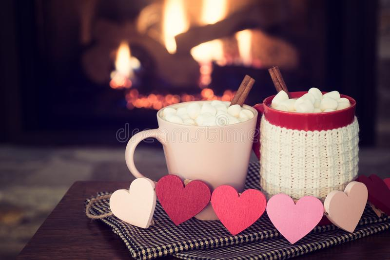 Romantic Valentine`s Day Fireplace Scene with Red and Pink Cocoa Mugs and Wood Hearts Garland in Cozy Setting with room or space f stock images