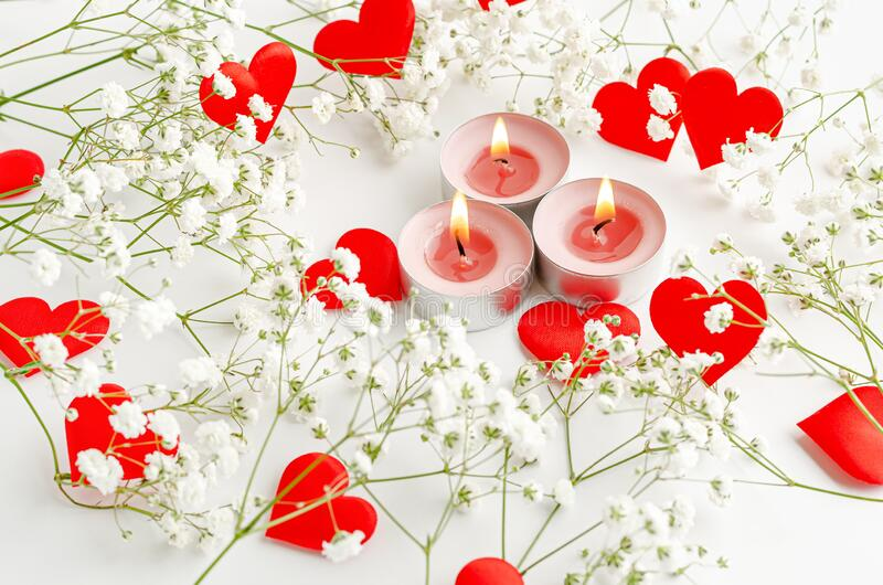 Romantic Valentines Day background. Burning candles and red hearts decorated with flowers. On white stock photography