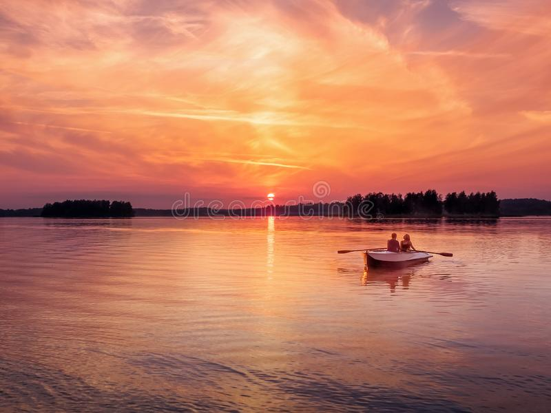 Romantic vibrant sunset river lake fog loving couple small rowing boat date beautiful Lovers ride during Happy woman man stock images