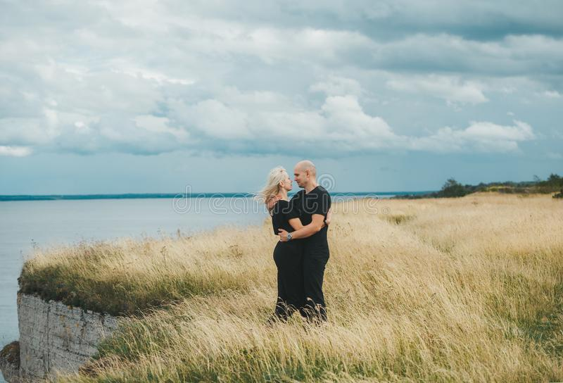 Romantic view of couple in black clothes when they embrace on the edge of the rocky coast of the Baltic sea stock images