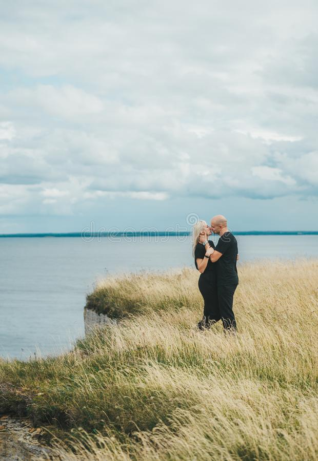 Romantic view of couple in black clothes when they kiss on the edge of the rocky coast of the Baltic sea royalty free stock photos